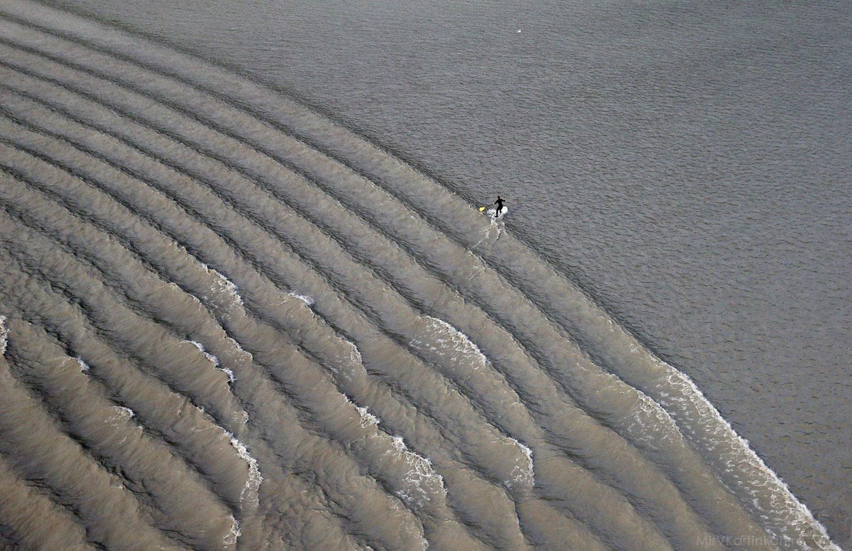 Серфер преодолевает волны
