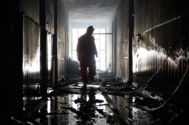 Пожарный внутри обугленного здания