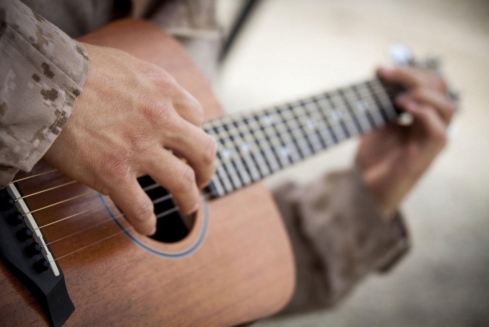 капрал морской пехоты США играет на гитаре