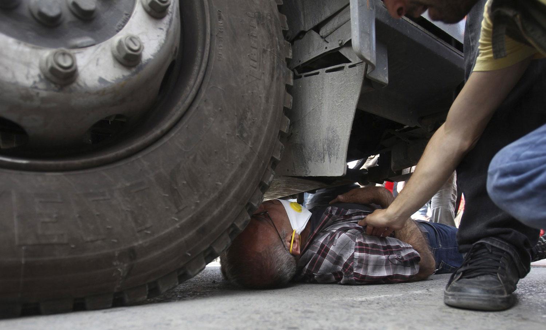 мужчина под колесами автомобиля