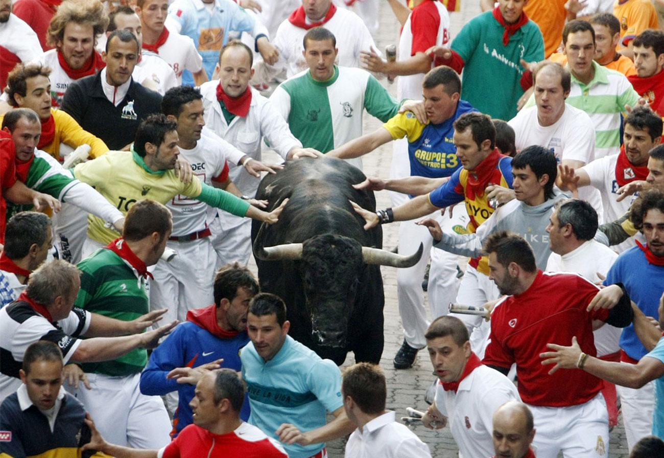 участники корриды бегут с быками