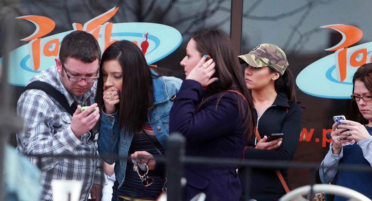 люди смотрят по телефону новости с места трагедии