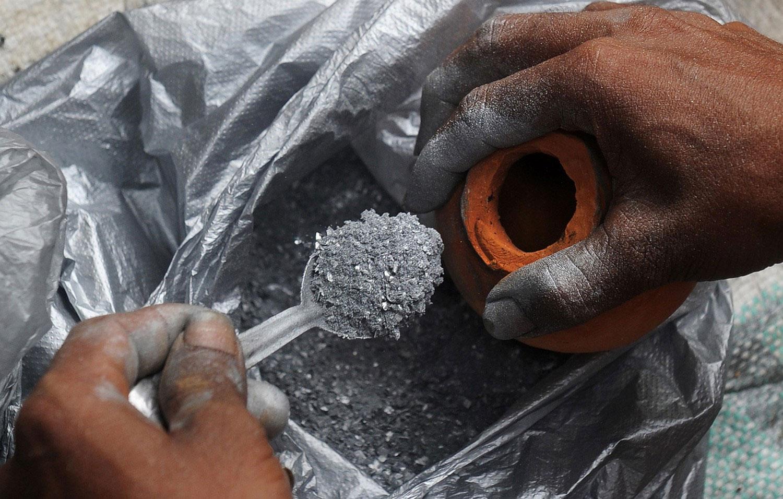 работник насыпает порох в глиняный горшок на фестивале, фотография 2012 года