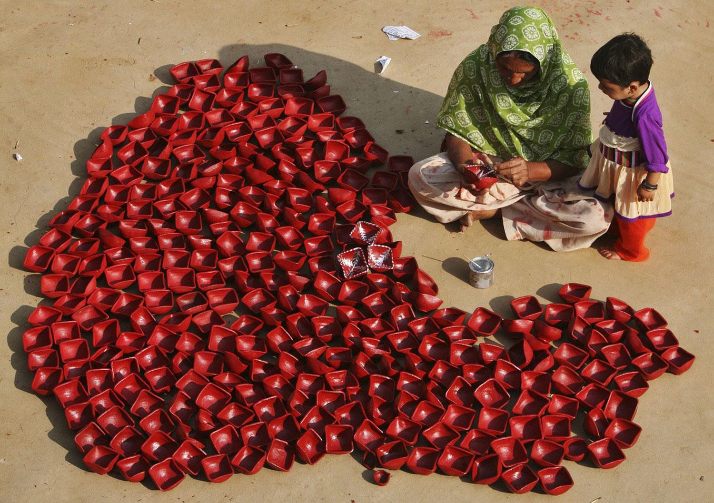 женщина рисует на горшках из глины