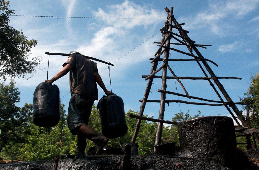 работник с нефтью, фото из Индонезии