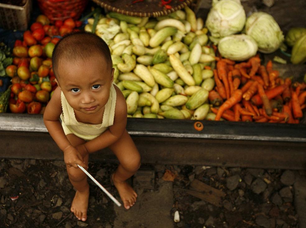 ребенок у овощного рынка, фото из Индонезии