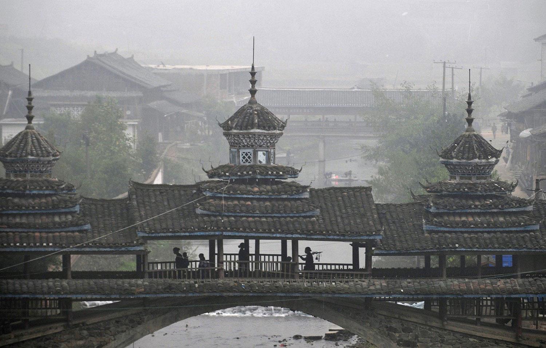 китайцы идут по крытому мосту, фото