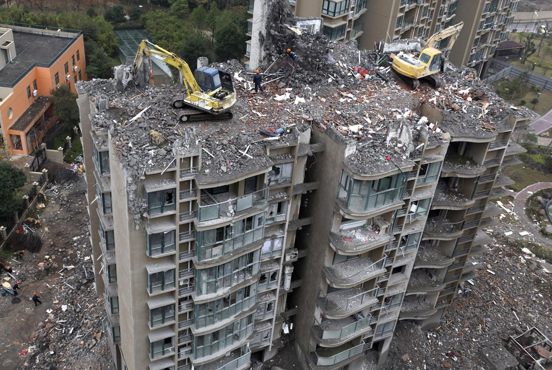 экскаваторы на крыше разрушенного здания, фото