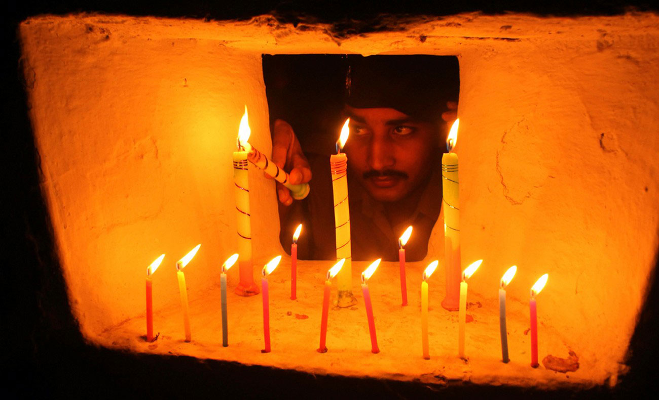 солдат зажигает свечи на фестивале огней в Индии
