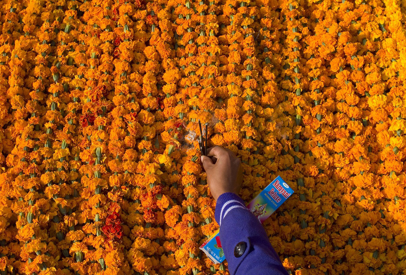 свечи среди цветов на рынке в Непале