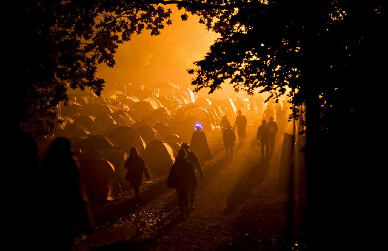 Люди идут через кемпинг, фото Гластонбери