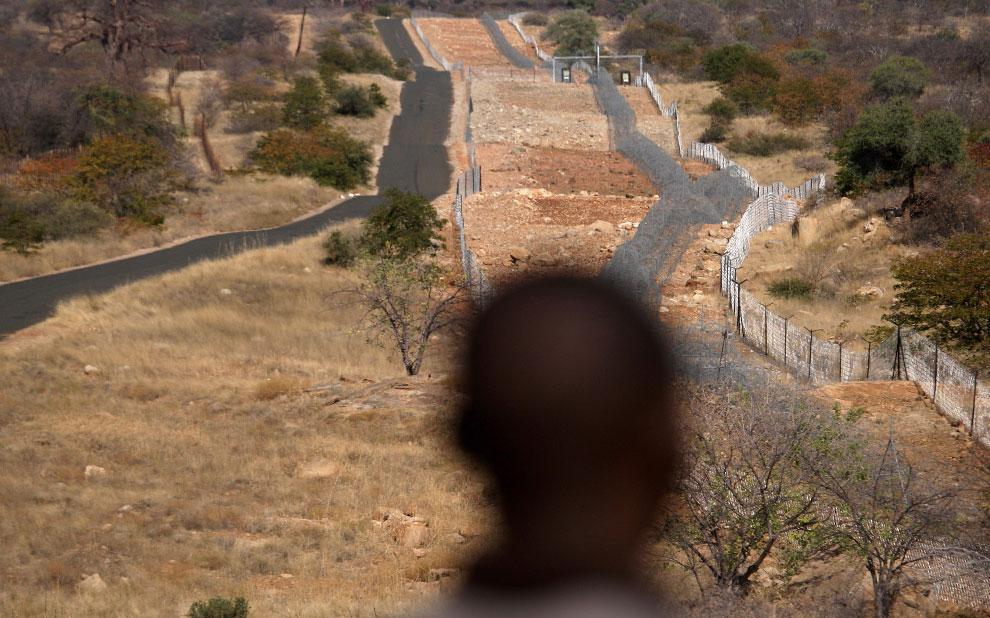 Беженец смотрит на пограничный забор