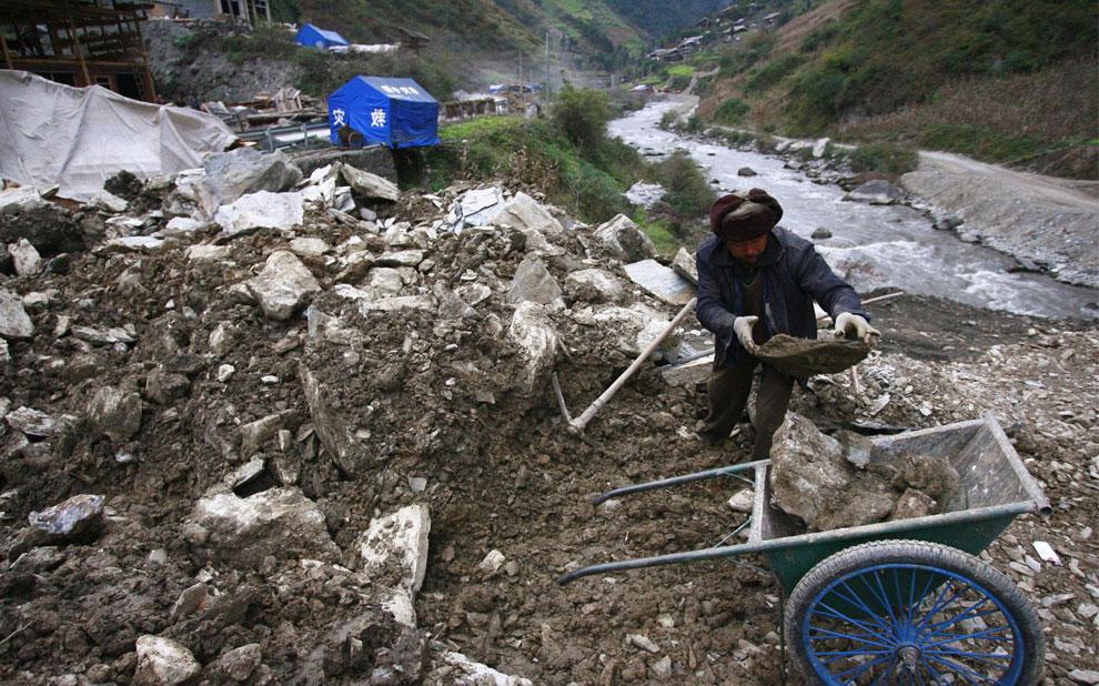 житель собирает камни для дома, Бэйчуань, Китай фото
