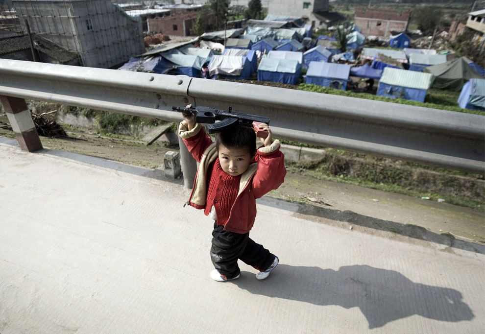 ребенок с игрушечным ружьем, Бэйчуань, Китай фото