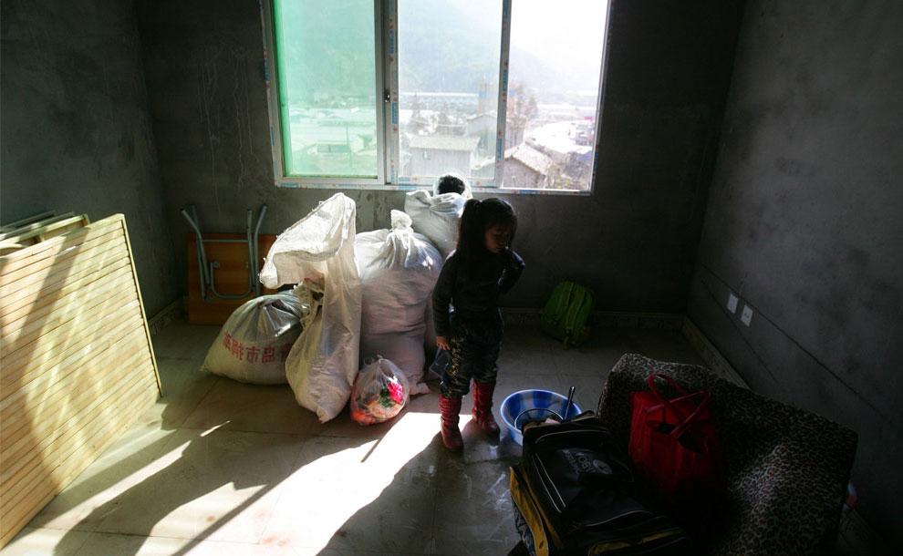 Девочка разбирает вещи после переезда, Бэйчуань, Китай фото