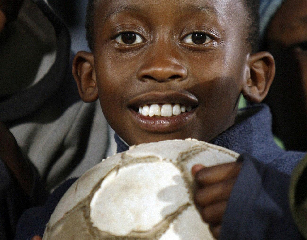 Ребенок с футбольным мячом на стадионе, фото