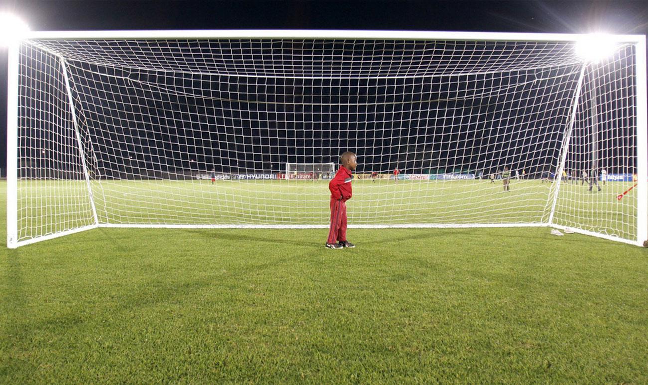 мальчик стоит на воротах на стадионе, фото