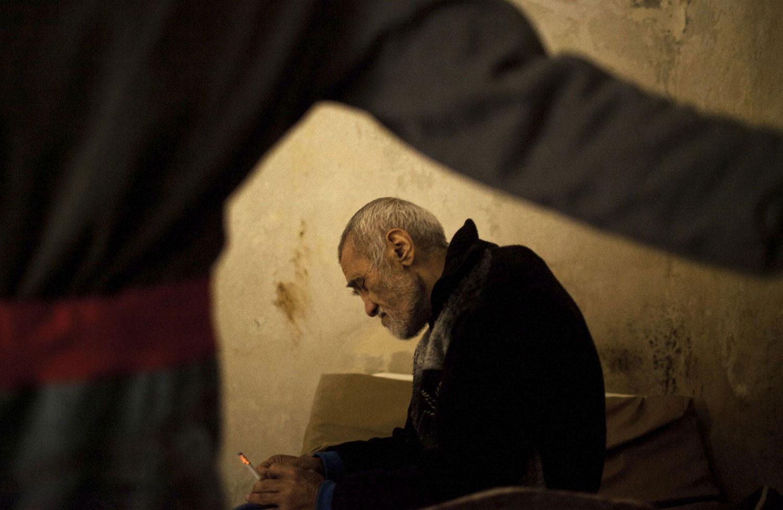 Мужчина курит в одной из палат психиатрии Сирии, фото