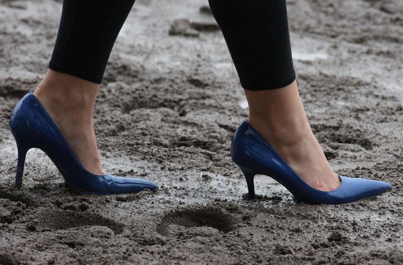 журналистка ходит по грязи на ипподроме, фото
