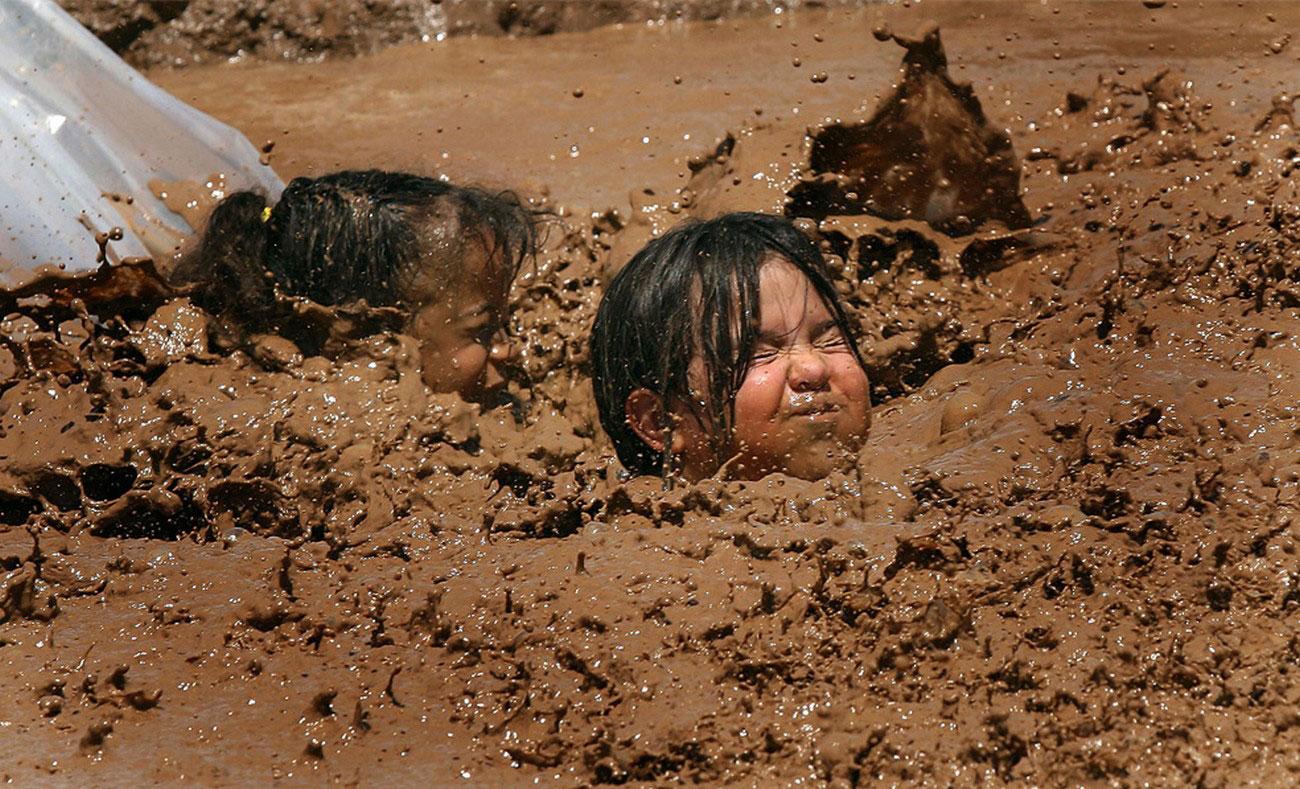 дети скатились с горки в огромное грязевое озеро