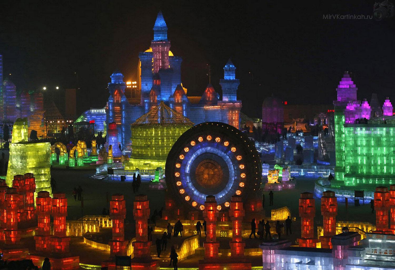 Первые посетители любуются ледяными скульптурами, которые освещены разноцветными огнями. Снимок сделан накануне открытия фестиваля в северном городе Харбине, провинция Хэйлунцзян, Китай.