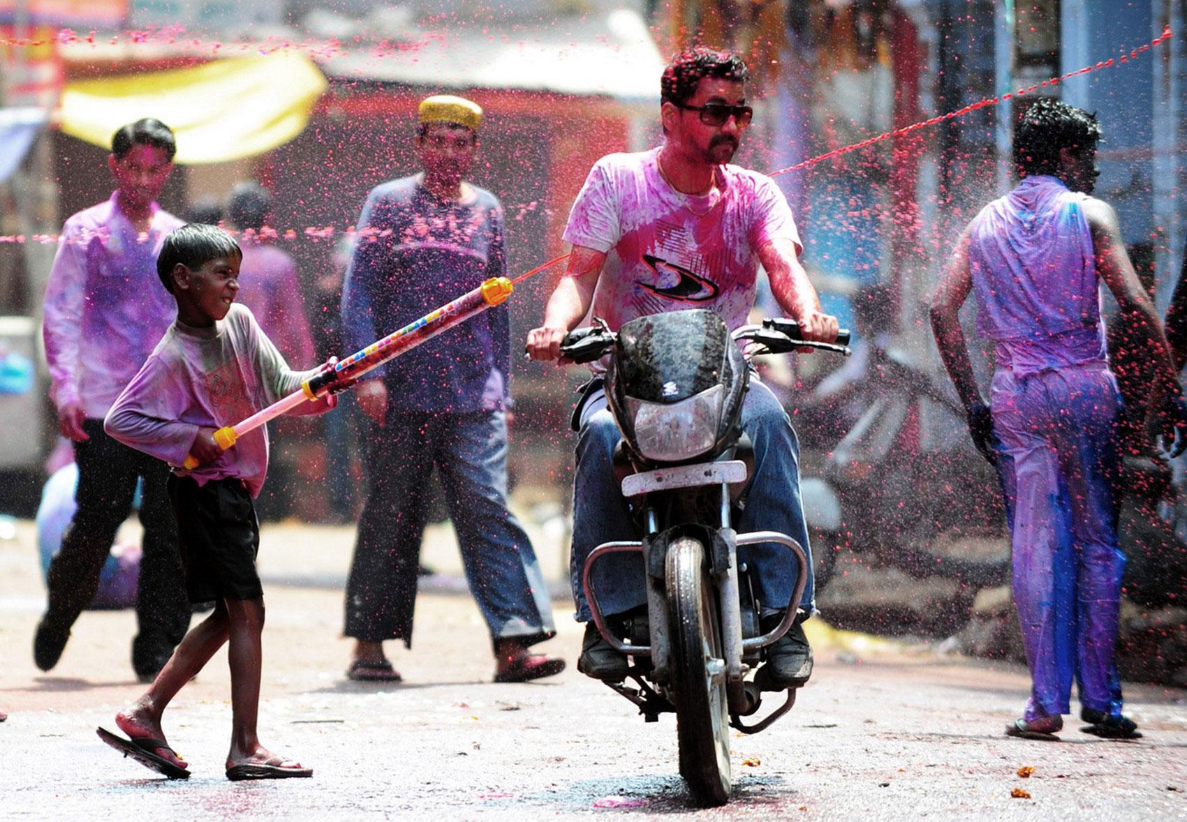 Мальчик поливает мотоциклиста красками