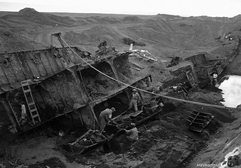 Рабочие убирают останки военно-морского судна
