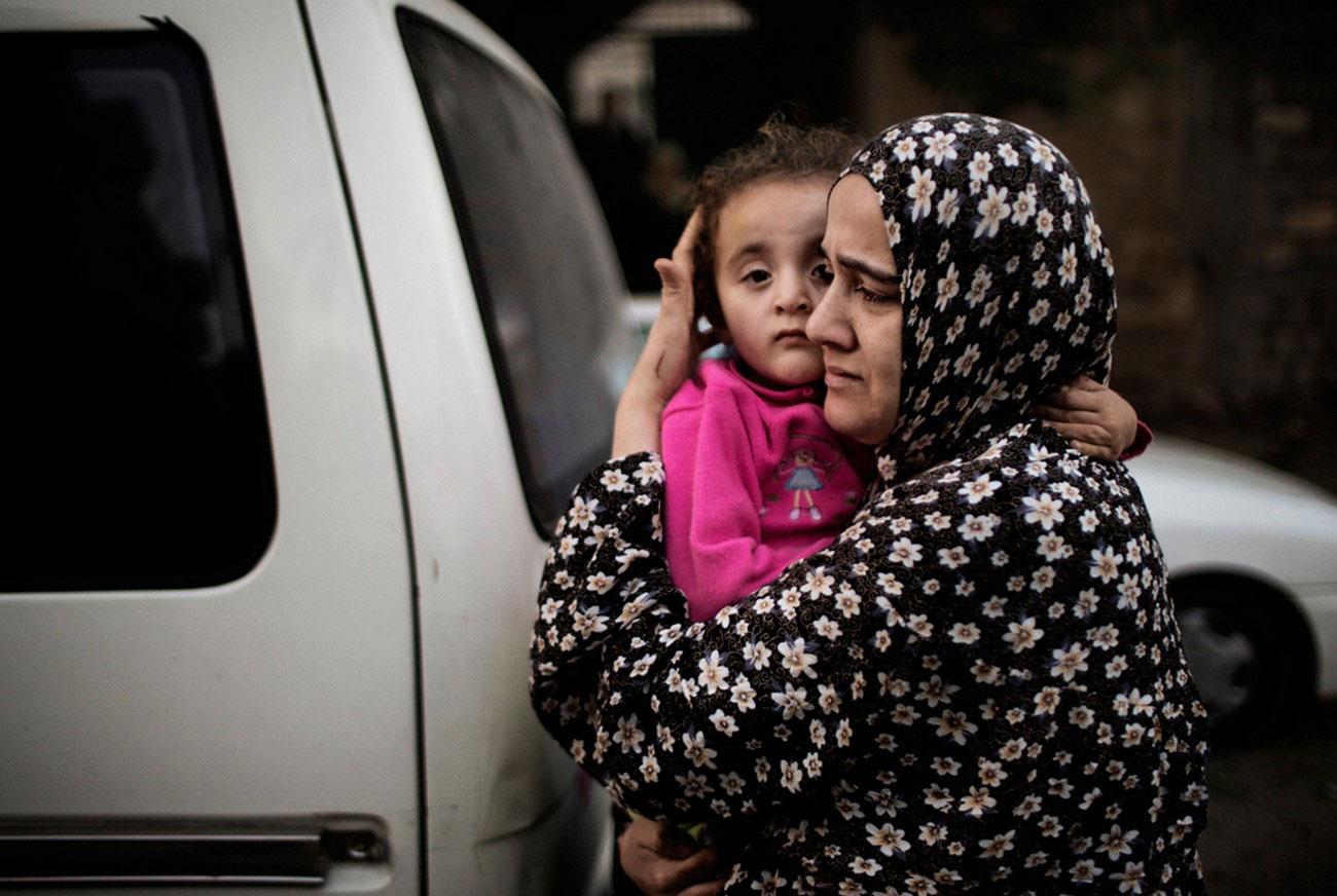женщина с ребенком бегут из разрушенного здания