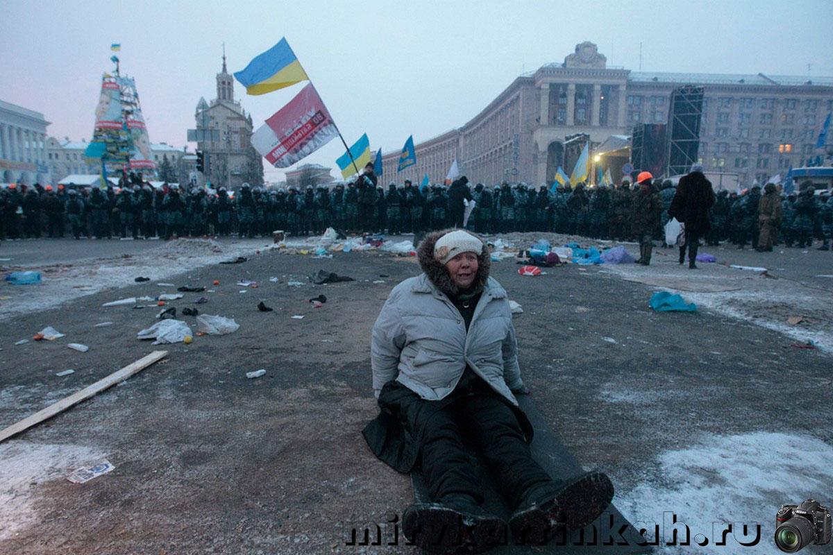 Женщина сидит посреди площади
