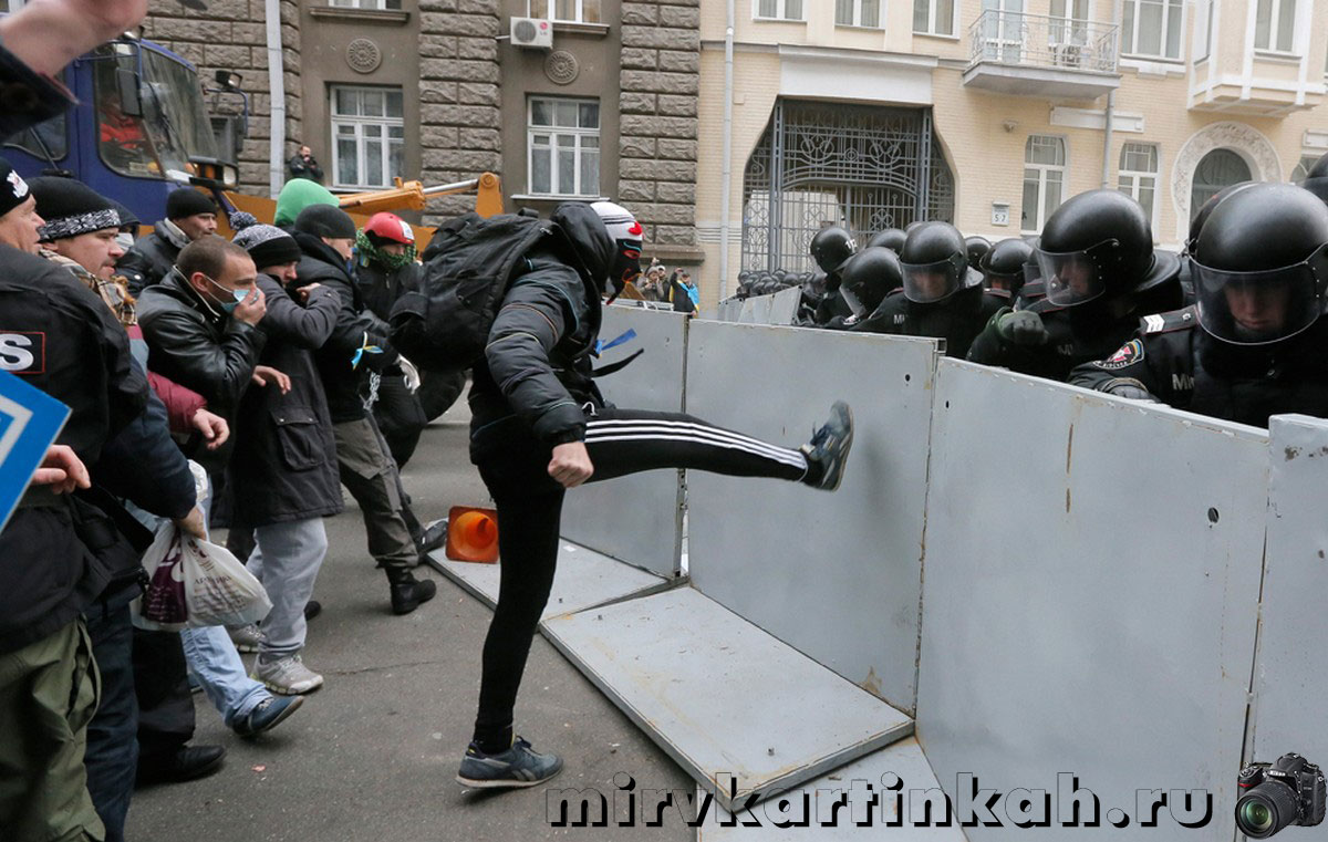 человек пинает полицейские заграждения