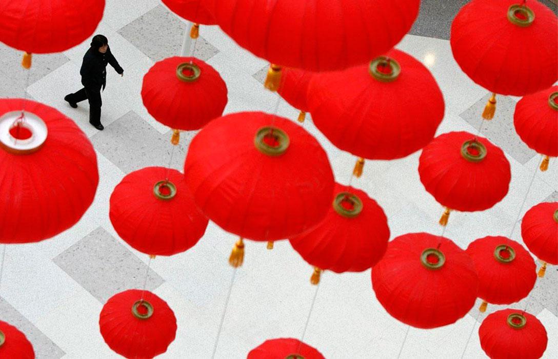 Женщина проходит под красными фонарями, фото