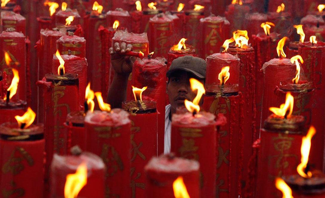 Человек зажигает свечи в храме, фото