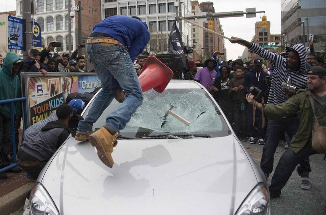 Демонстранты разбивают лобовое стекло