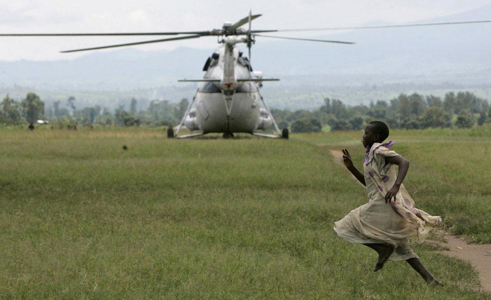 Ребенок пробегает мимо вертолета ООН, Конго, фото