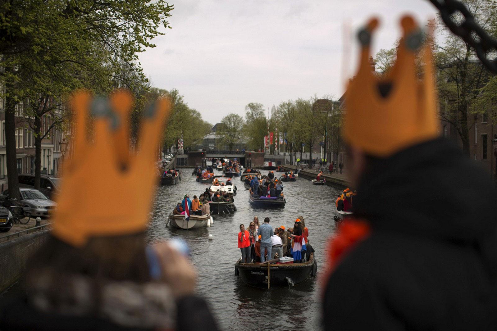 люди плывут на лодках по каналам Амстердама