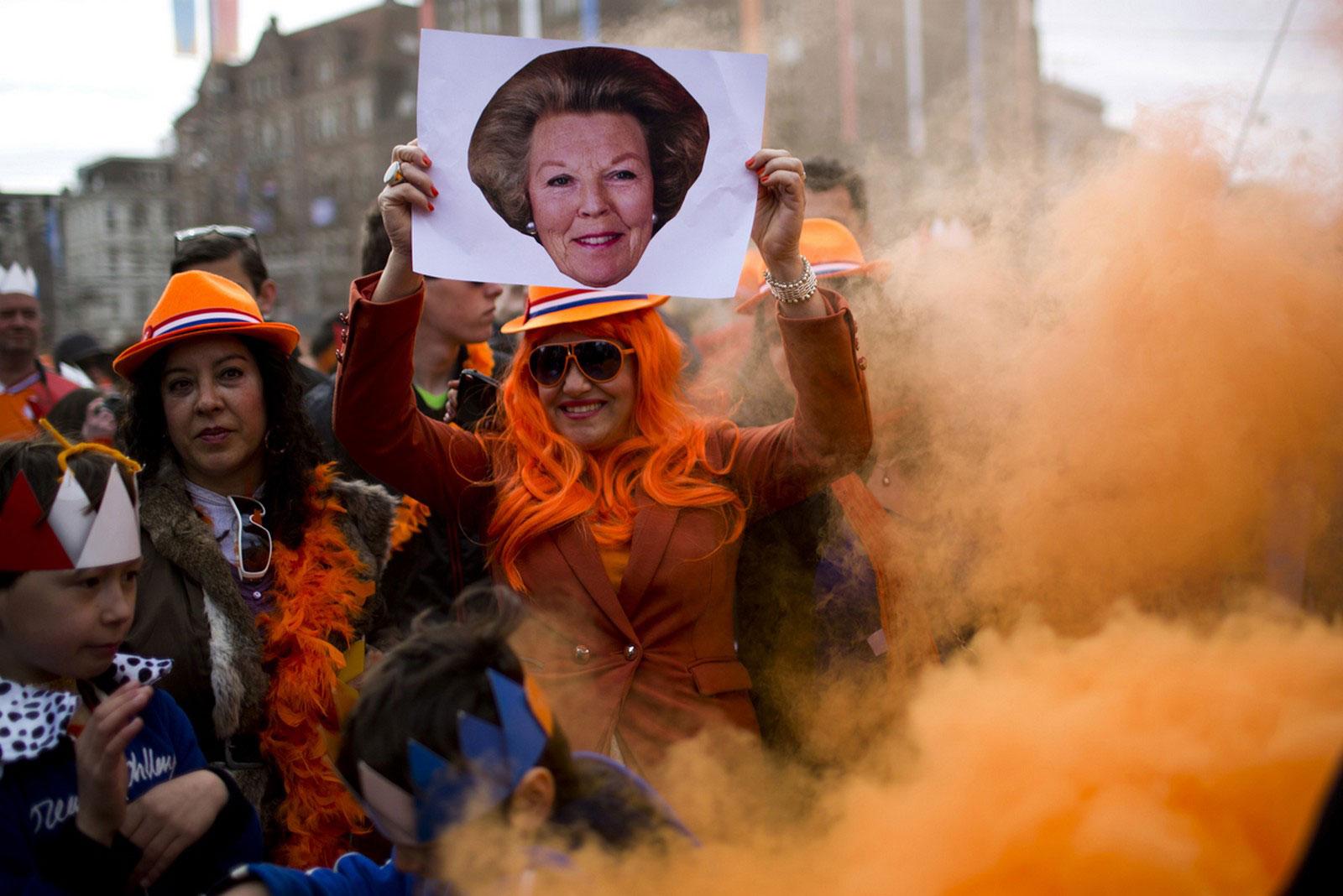 Женщина держит портрет королевы Беатрикс