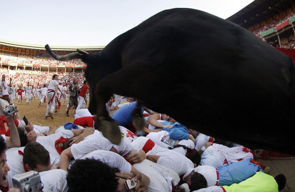 фото быка, прыгающего через участников корриды