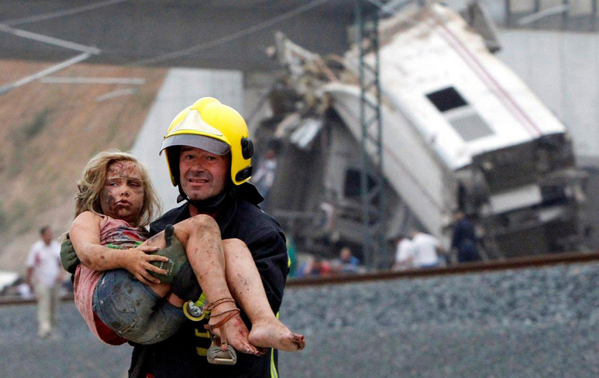 Пожарный несет раненую девочку