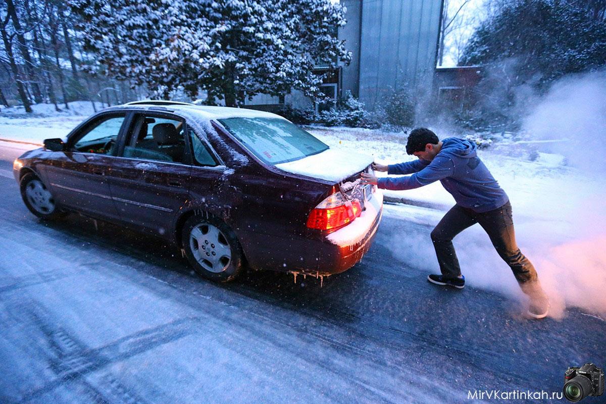 Мужчина толкает автомобиль