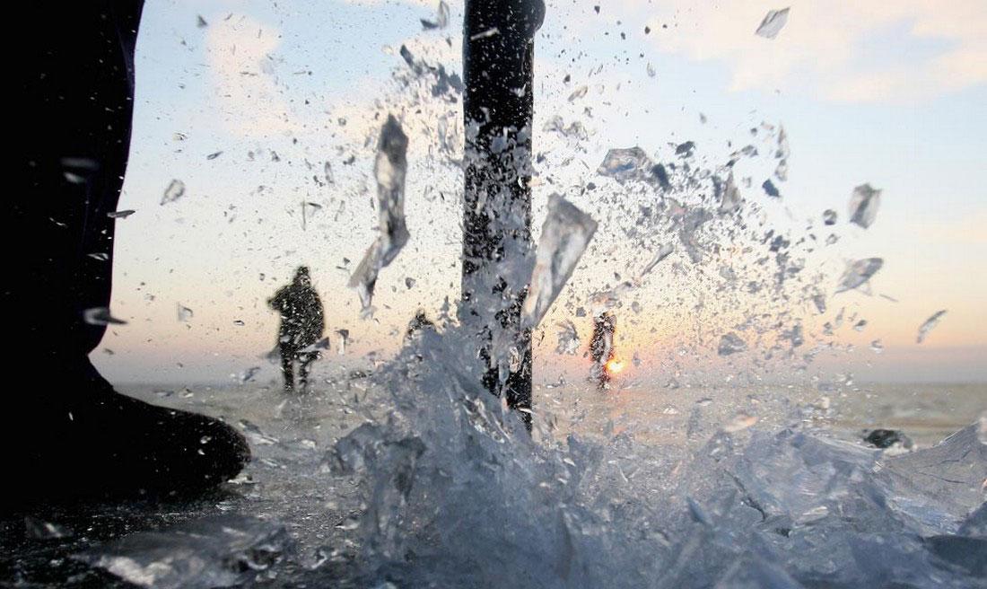 Рыбаки проделывают во льду отверстие, фото