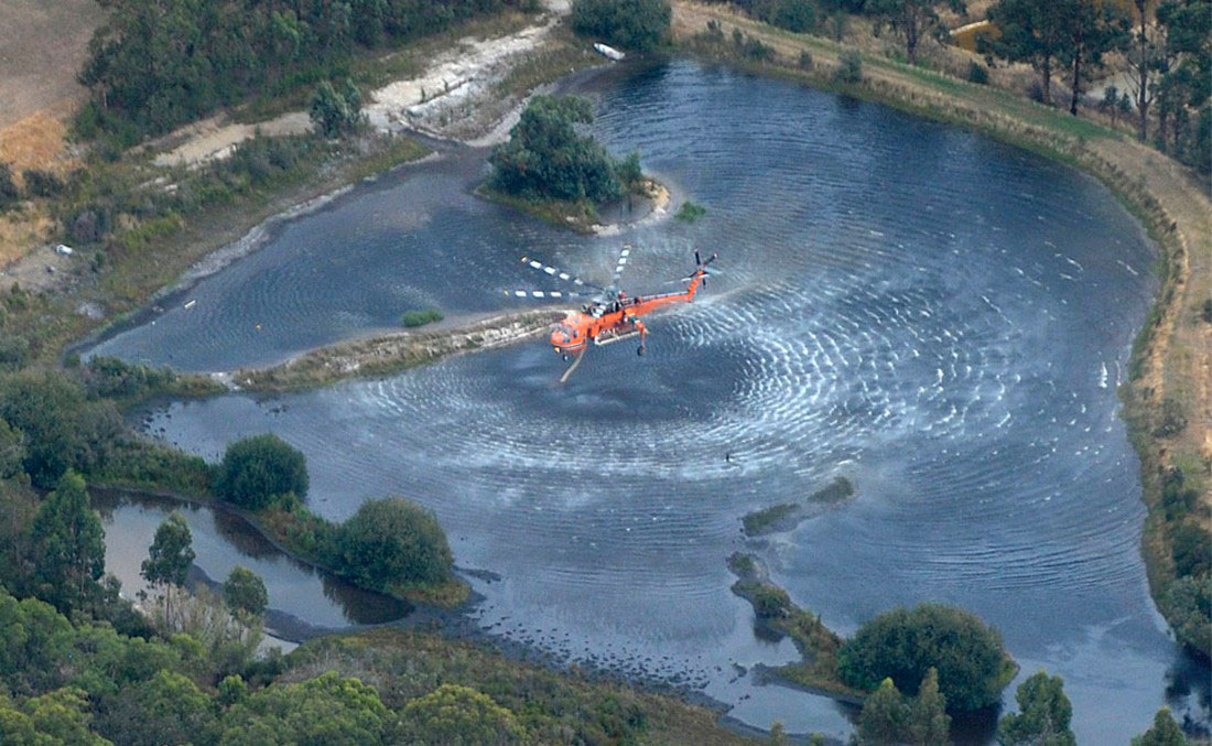 Пожарный вертолет собирает воду, фото из Австралии
