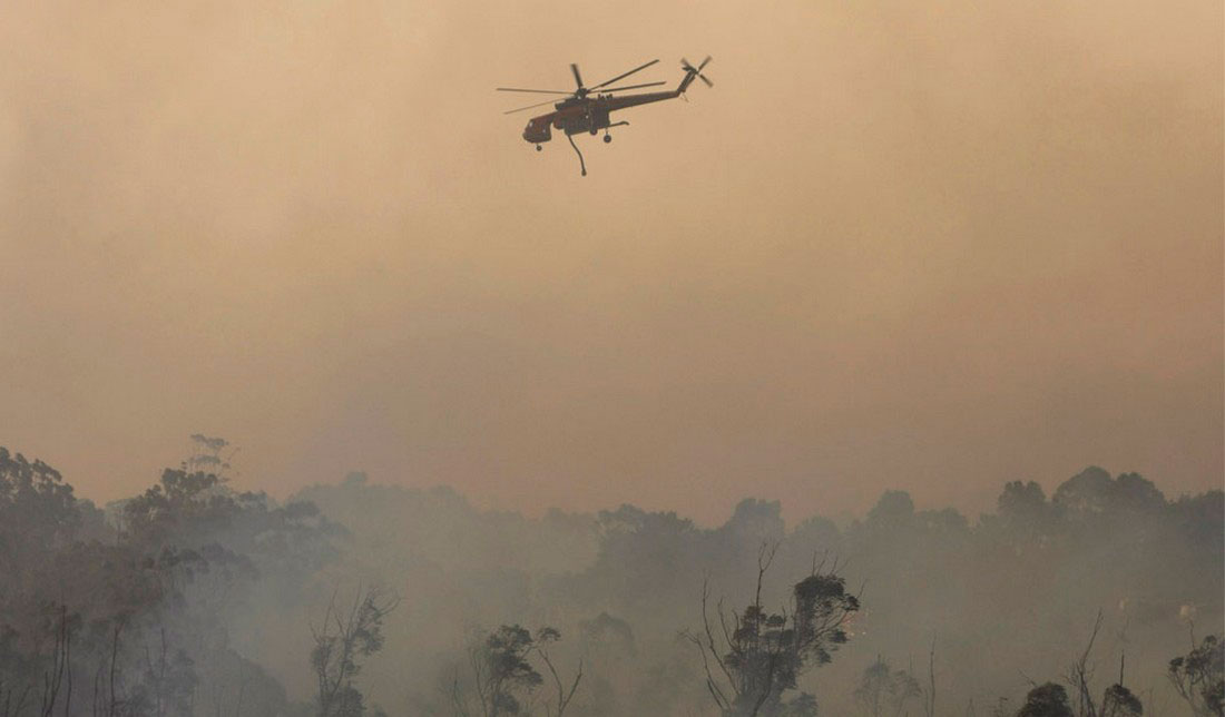 Вертолет сбрасывает воду на охваченные огнем окрестности, фото из Австралии