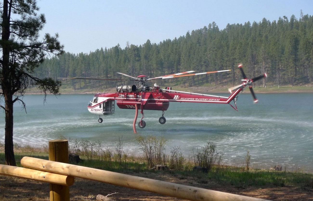 Пожарный вертолет набирает воду, фото лесных пожаров