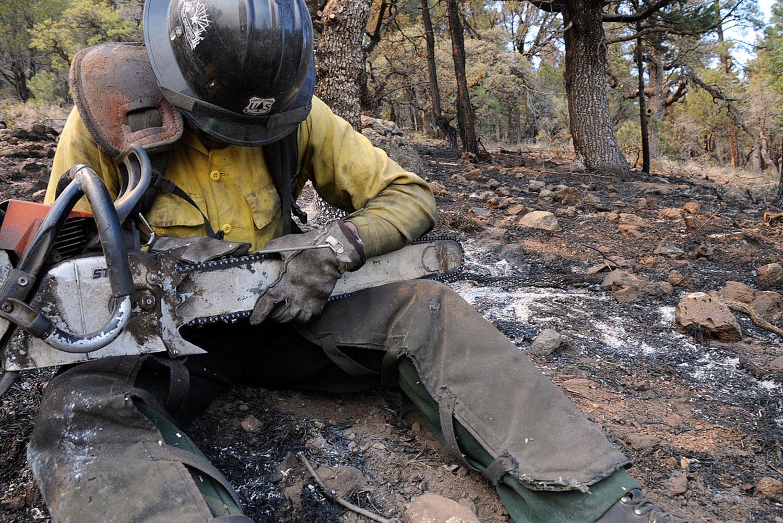 Пожарный чистит пилу, фото
