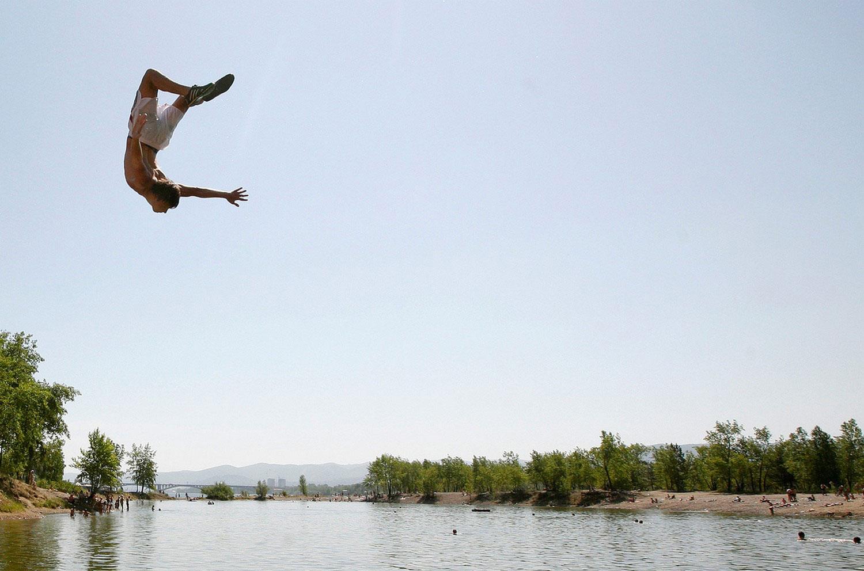 Человек прыгает в озеро, фото летнее