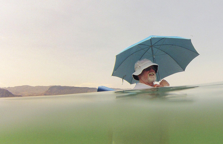 мужчина под зонтиком в воде