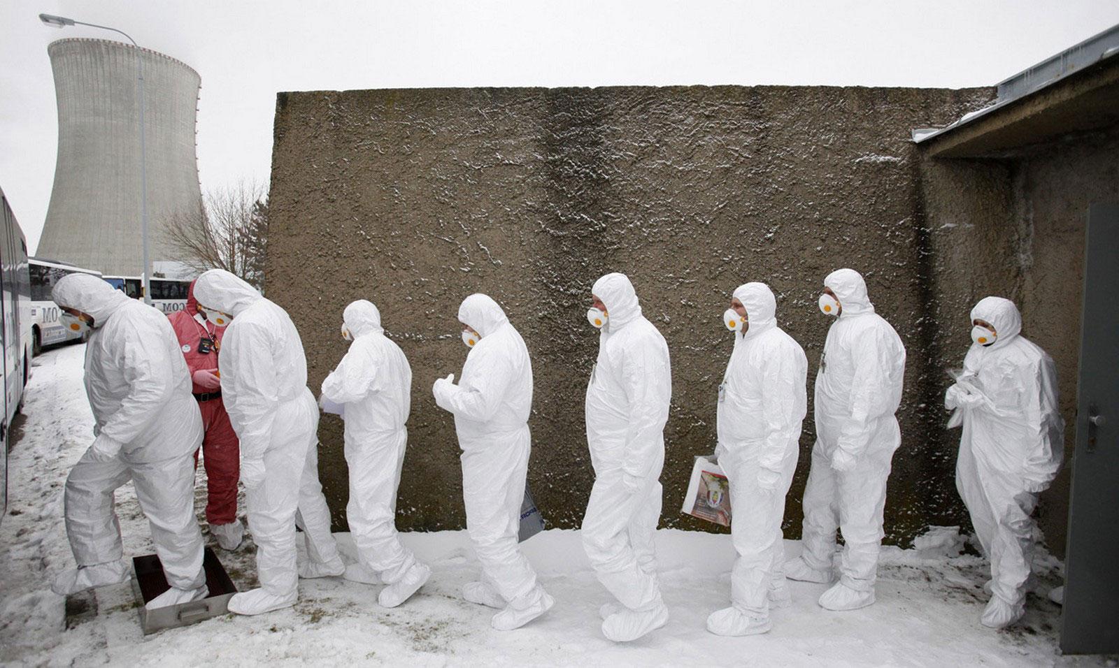 Рабочие в защитных костюмах