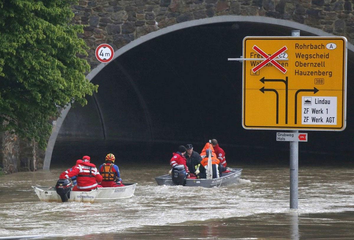 Люди передвигаются на лодках по затопленным улочкам