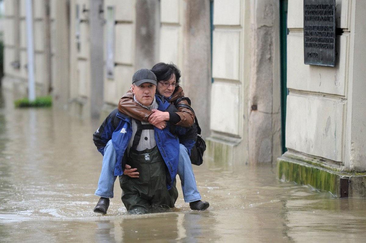 Мужчина помогает женщине спастись от наводнения