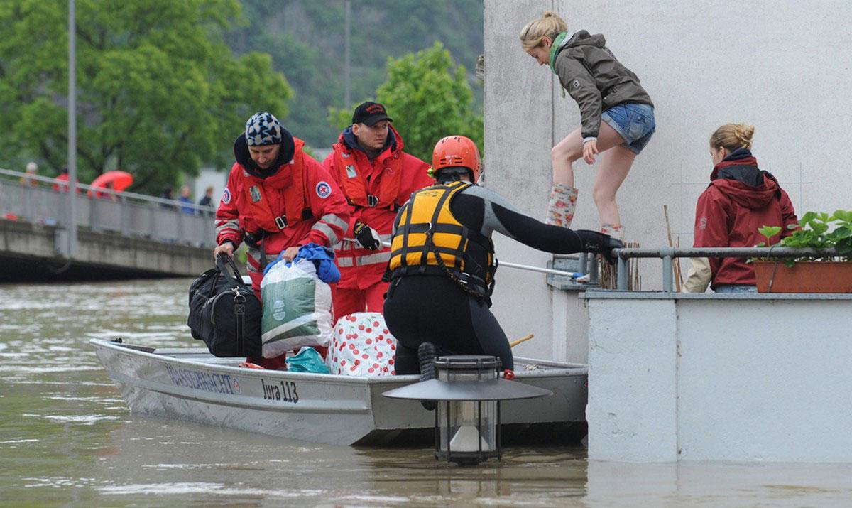 Две женщины перебираются в лодку спасателей